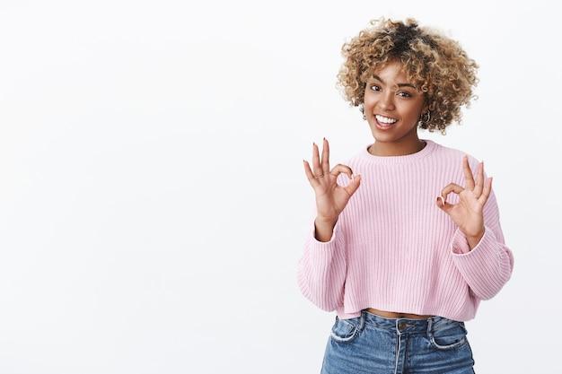 Охладите все идеально. портрет счастливой и довольной женщины-покупательницы афроамериканского происхождения, рекомендующей продукт хорошего качества, демонстрирует жест `` ок '' и удовлетворенно улыбается над белой стеной Бесплатные Фотографии