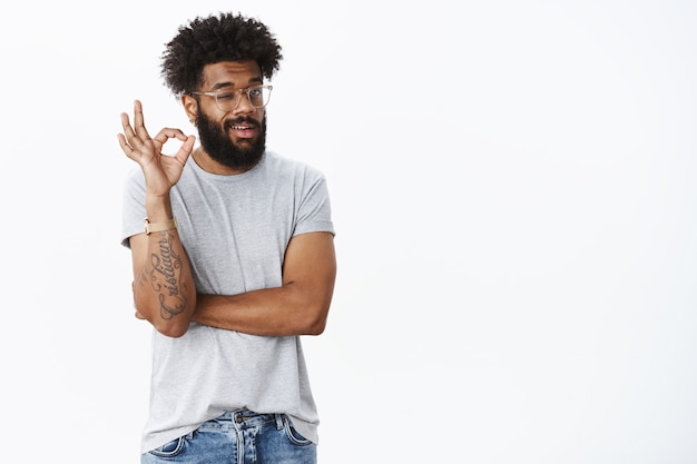 冷静で前向きなアフリカ系アメリカ人の男性の友人が承認と確認でウィンクし、心配することなく大丈夫なジェスチャーを示し、前向きな意見を述べ、灰色の壁の上の完璧な計画に満足しています