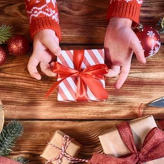 クリスマスギフト用の箱、クリスマスの休日の背景を持つ冷えた手