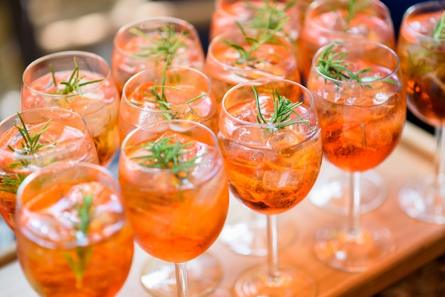 Chilled alcoholic cocktails served on the rocks with rosemary garnish displayed in rows on a buffet table in elegant glasses at a catered event