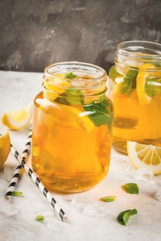 Chilled summer tea with ice, mint and lemon.
