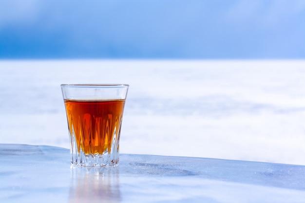 Охлажденный виски в стакане стоит на льду на фоне размытого снега и неба. апельсиновый алкогольный напиток в стакане. скопируйте пространство. вид сбоку. фон размытый. по горизонтали.