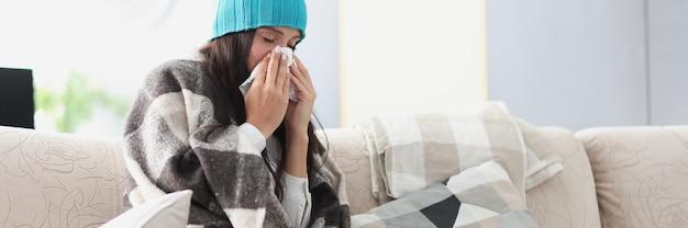毛布と帽子のソファで冷やした女性はハンカチを保持します
