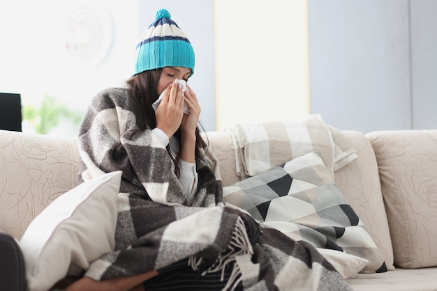 Chilled woman on sofa in blanket and hat holds handkerchief