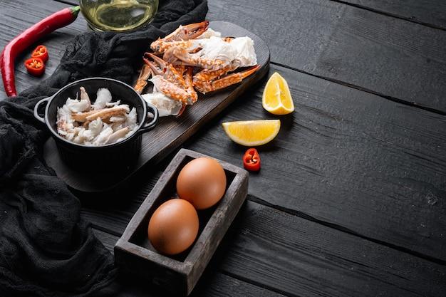 Набор ингредиентов шелковистого омлета с крабом чили, на черном фоне деревянного стола, с copyspace и местом для текста