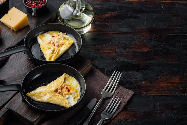 Шелковистый омлет с крабом и перцем чили, на сковороде, на темном деревянном фоне, с copyspace и местом для текста