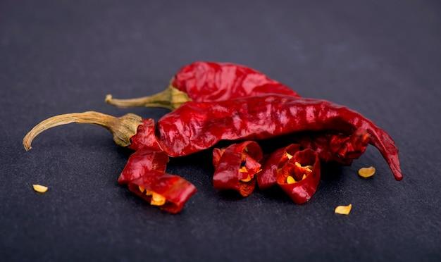 Chilli pepper, dry pepper, paprika, spice on slate black stone plate