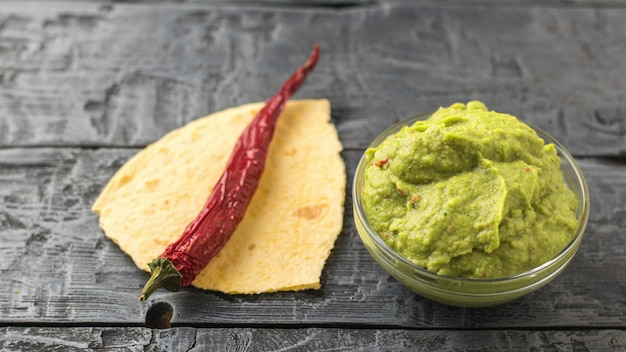 Chilli pepper on pieces of pita and fresh guacamole in bowl on the table