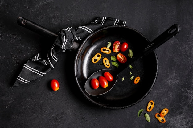 Chilli pepper and tomatoes in black frying pan flat lay