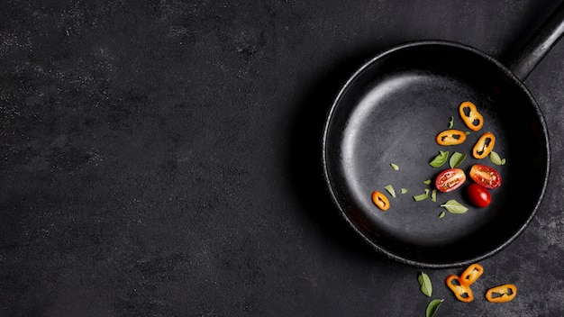 Chilli pepper and tomatoes in frying pan with copy space background