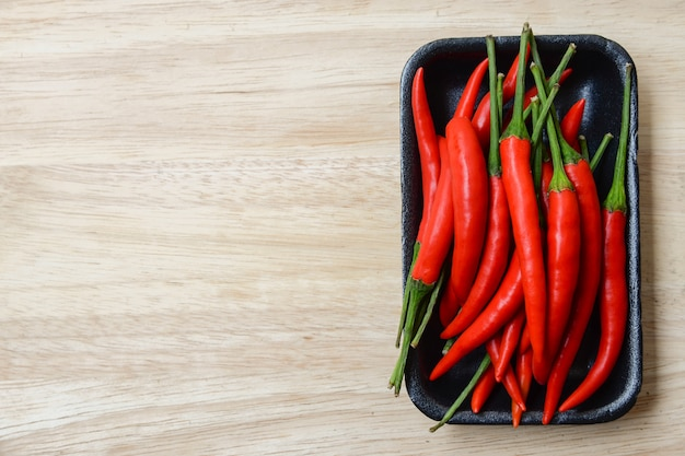 Chilli peppers on black plastic plate with bright wood