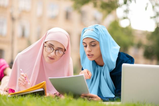 身も凍るような読書。レーンで身も凍るようにヒジャーブで読書をしている2人の勤勉なイスラム教徒の学生