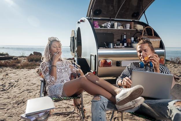 身も凍るような喫煙。彼女の男の近くに座って喫煙タバコを冷やすドレッドヘアを持つスリムでモダンなスタイリッシュな女性