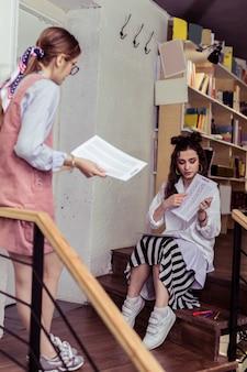 チリングエリア。木製の階段に座って、彼女の手で紙を指して長い縞模様のスカートの黒髪の女性