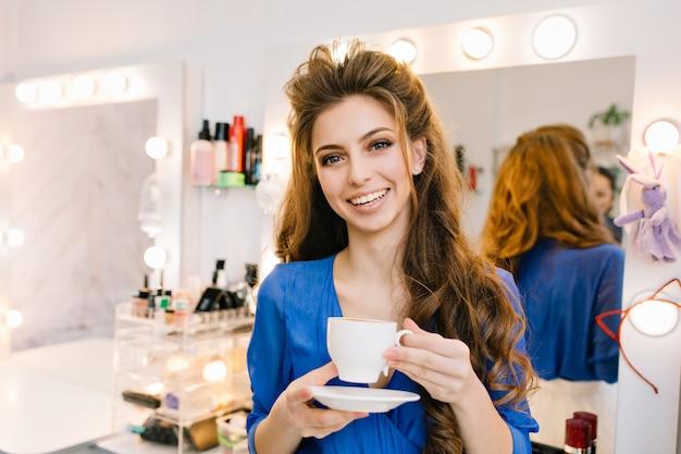 Raffreddare nel salone di bellezza della giovane donna bruna gioiosa con una bella acconciatura sorridente alla telecamera con una tazza di caffè