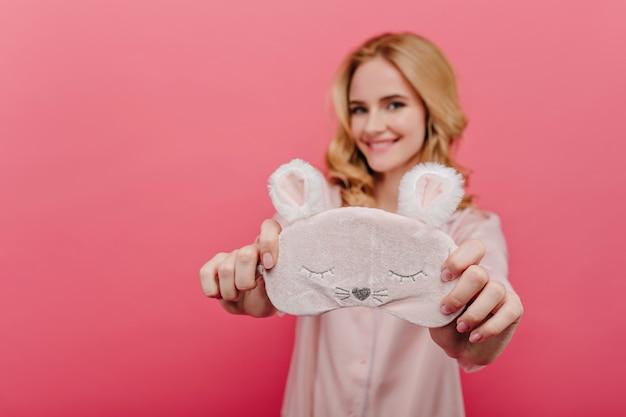 かわいいsleepmaskを保持している身も凍るようなブロンドの女の子。おはようございます幸せを表現するシルクパジャマで前向きな女性を笑う。