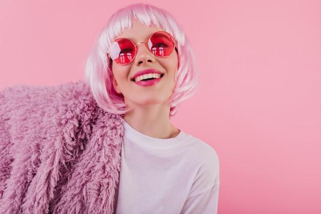 Охлаждающая кавказская девушка позирует в солнцезащитных очках и модном перуке. веселая молодая женщина с розовыми волосами смеется