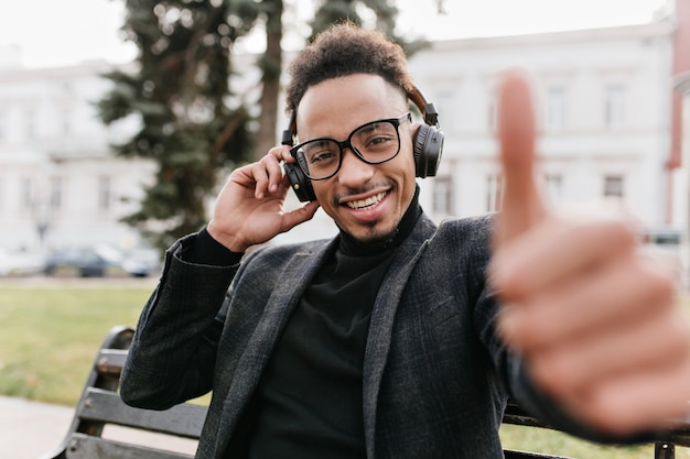 Chilling curly african boy posing with thumb up. outdoor portrait of cheerful black guy in dark attire having fun on the street.
