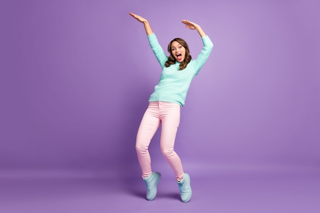 Chilling funny lady raise hands dancing youth modern moves crazy student wear casual fluffy pullover pastel pink pants shoes.