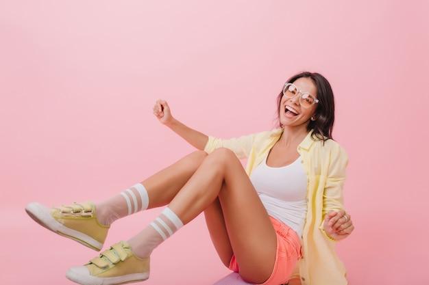 床に座っているかわいい黄色のスニーカーで身も凍るような女の子。リラックスできる明るい服装の愛らしいヨーロッパのブルネットの女性