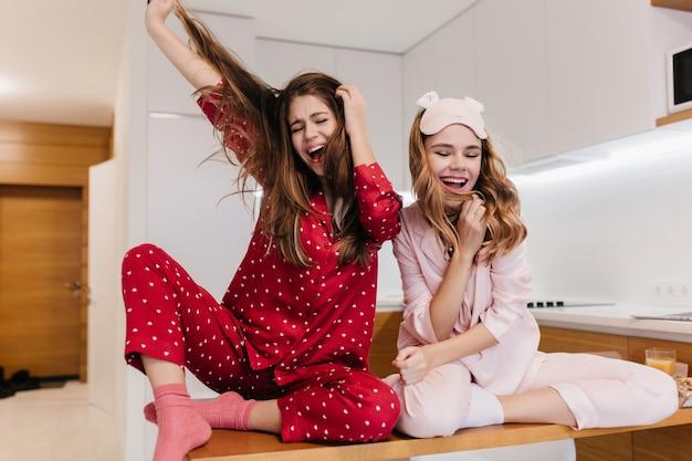 Пугающая девушка в розовых носках, сидя на деревянном столе. крытое фото милой молодой женщины в розовой пижаме, развлекающейся на кухне.