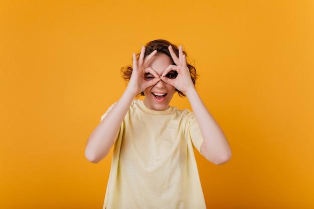 明るくカラフルなインテリアを楽しんでいる短いウェーブのかかった髪の寒い女の子。黄色のtシャツを着た熱狂的なブルネットの淡い女性の写真。