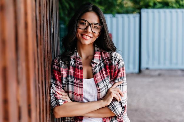 腕を組んで笑いながら路上でポーズをとる冷静なラテン系の女の子。恥ずかしがり屋の笑顔で立っている美しいブルネットの女性。