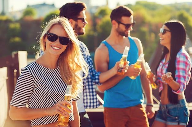 Отдыхать с друзьями. улыбающаяся молодая женщина держит бутылку пива и смотрит в камеру, пока три человека разговаривают друг с другом на заднем плане