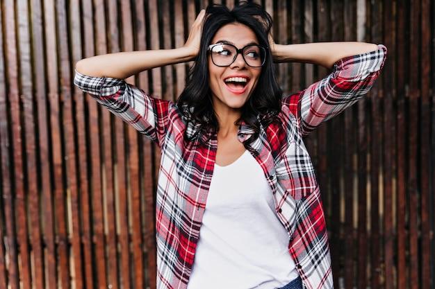 木製の壁に彼女の黒い髪に触れている身も凍るような日焼けした女の子。眼鏡をかけた壮大な幸せな女性の写真。
