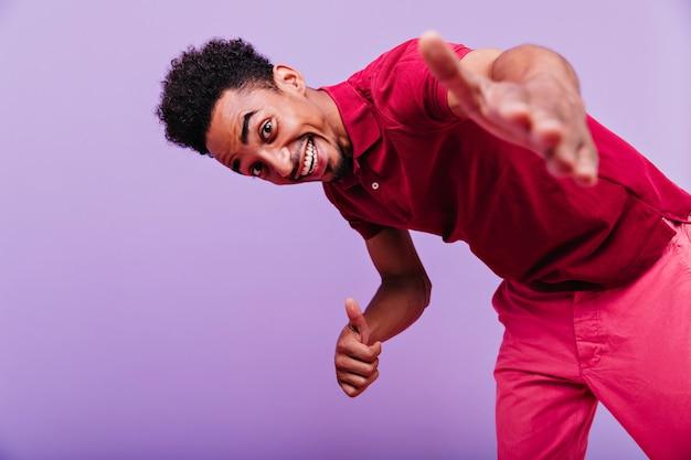 紫の壁にポーズをとっている身なりのよい黒人の男を冷やす。楽しんでいる至福のブルネットの男。