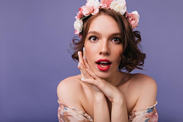 헤어 스타일 찾고있는 장미와 함께 재미있는 백인 여자. 꽃의 화 환에 웅장 한 짧은 머리 아가씨의 실내 촬영.