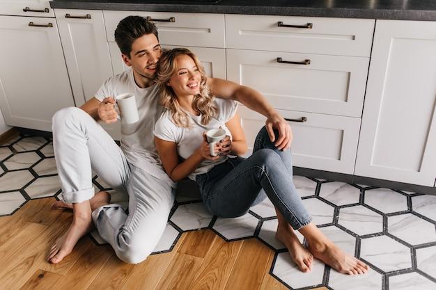 週末の朝にコーヒーを飲む寒い若者。朝食時にリラックスした笑顔のカップルの屋内の肖像画。