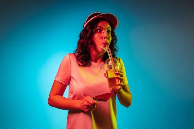 トレンディな青いネオンスタジオでお菓子と飲み物を保持している帽子で身も凍るような若い女性