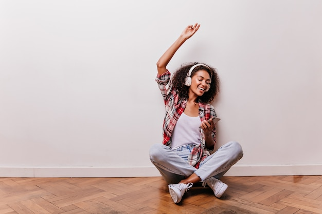 Chilling young woman sitting on the floor and listening music. amazing african girl posing with legs crossed while enjoying favorite song.