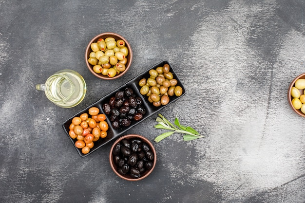 Chilly olives assortment in a black plate and clay bowls with a jar of olive oil and olive leaves top view on dark grey grunge
