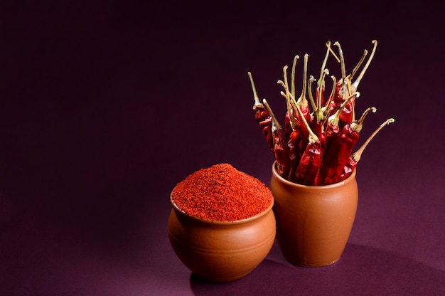 Chilly powder in clay pot with red chilly on wooden background