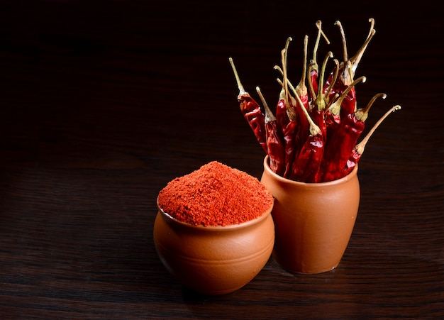 Холодный порошок в глиняном горшочке с красным чили на деревянном фоне