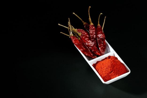 Холодный порошок с красным чили в белой тарелке, сушеный перец чили на черной поверхности