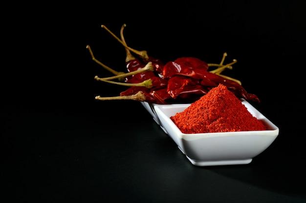 Холодный порошок с красным чили в белой тарелке, сушеный перец чили