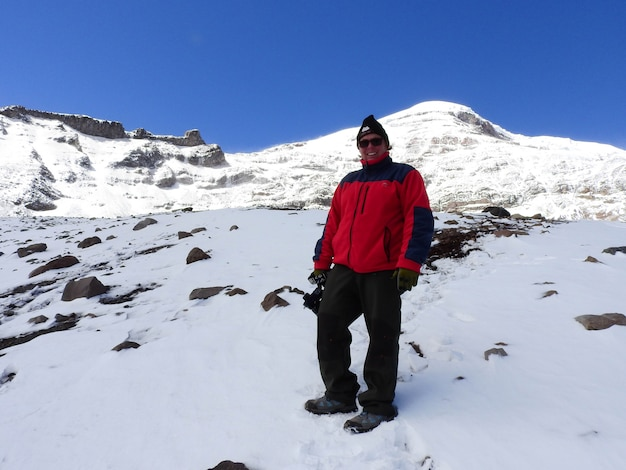 Chimborazo volcano covered in snow and a hiker