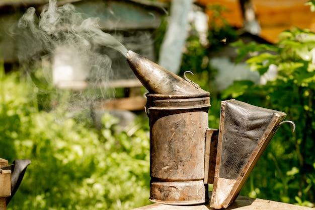 Дымоход для мигания пчел. дымоход стоит возле ульев. пчеловод