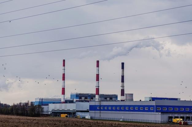 Дымоход на заводе тепловой электрогенераторной промышленности. загрязнение атмосферы и парниковый эффект