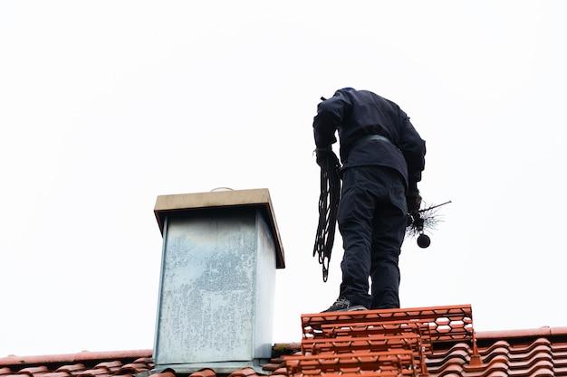 Трубочист на крыше дома работает Premium Фотографии
