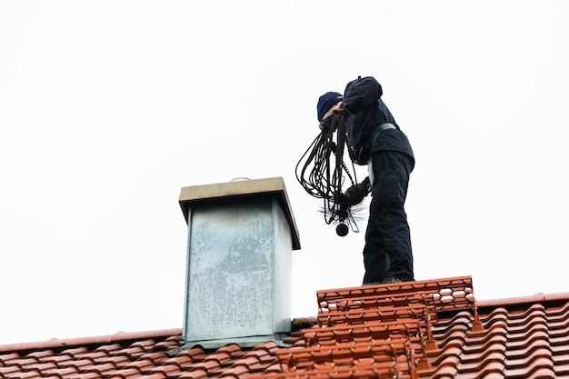 Chimney sweep on roof of home working