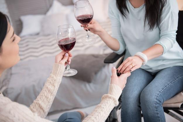 Подбородок подбородок. крупным планом женские руки, держащие бокалы, наполненные красным вином