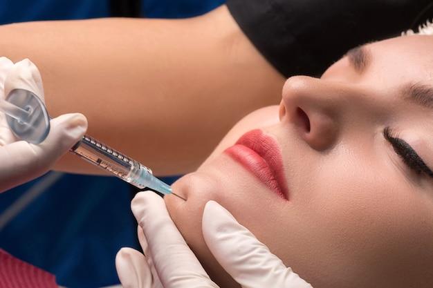 Липофилинг подбородка. женщина получает косметическую инъекцию ботулина