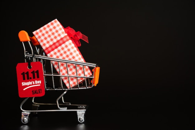 China, 11.11 single day sale, red ticket tag hanging on mini shopping cart with gift boxes