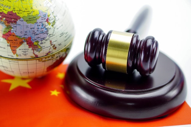 China flag and judge hammer with globe world map.