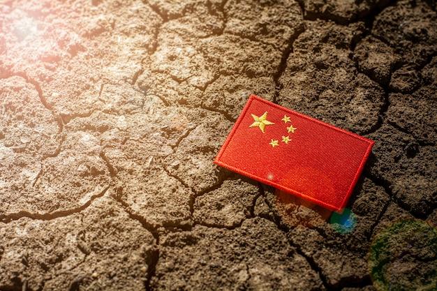 放棄された割れた地面に中国の旗。