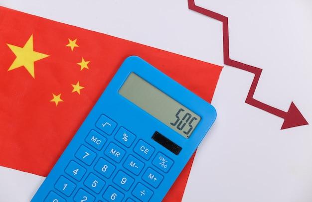 붉은 가을 화살표와 계산기 중국 국기입니다. 가을 그래프가 내려갑니다. 경제 불황, 위기